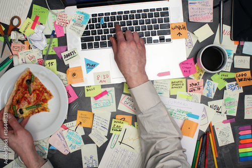 Fotomural  Top view on multitasking man working on laptop computer with post it notes all around his office desk