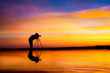 Leinwandbild Motiv Silhouette Photographer take photo dramatic colorful sunset sky