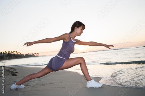 Tuinposter Gymnastiek femme qui fait de la gymnastique sur la plage au coucher du soleil