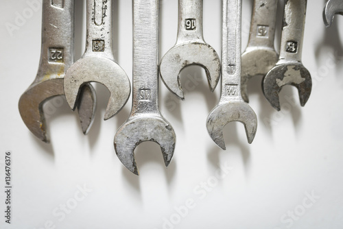 Close-up of wrenches hanging on white wall at workshop