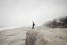 Side View Of Man Standing On Cliff At Beach During Foggy Weather
