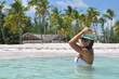 Smiling young girl in the clear blue water on the tropical beach with palm trees, Dominican Republic