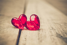 Love For Valentine's Day: Two Red Beads With A Shape Of A Heart On Wood Plank Floor