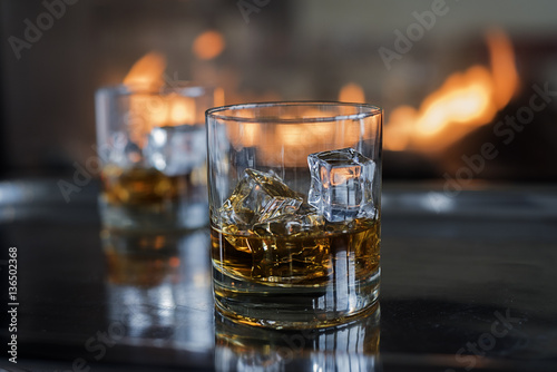 Two Scotch on the rocks cocktails by the fire