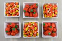 Six Square Bowls Of Candy Corns And Pumpkins