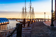 First light catches the bollards and heavy chains by the moored tall ships in Boston Harbor