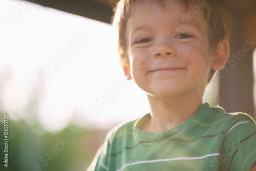 happy smiling blond caucasian kid outdoor portrait at park