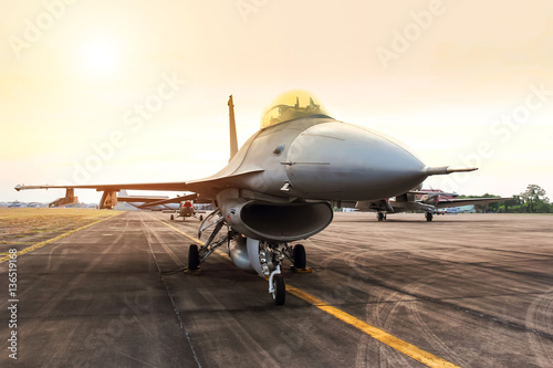 fototapeta na drzwi i meble falcon fighter jet military aircraft parked in the base airforce on sunset