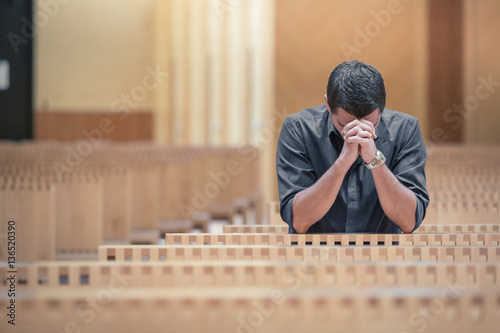 Fotografie, Obraz  Young beard man wearing blue shirt praying in modern church