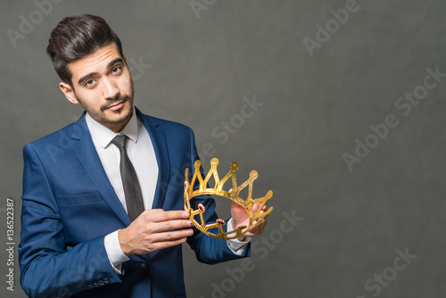 Fotografie, Obraz  Young attractive man in a blue suit holding in the hands of the crown on a gray