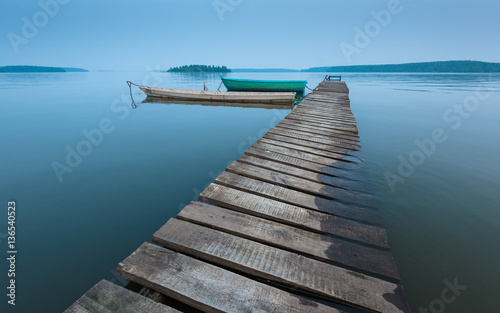 Photographie  meditative landscape with old wooden pier and wooden boats, long exposure