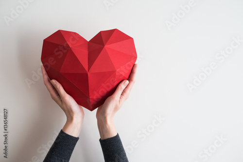 Leinwand Poster Two female hands holding red polygonal paper heart shape