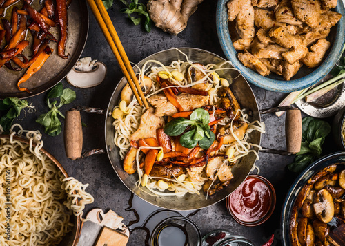 Foto  Asian kitchen table with food bowls, wok , stir fry , chopsticks and ingredients