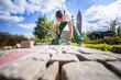 canvas print picture - Handwerker verlegt Pflastersteine in einer Gartenanlage