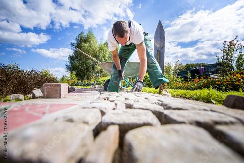 Fotografie, Obraz  Handwerker verlegt Pflastersteine in einer Gartenanlage
