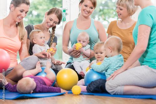 Cuadros en Lienzo Junge Frauen in Mutter-Kind-Gymnastik spielen mit ihren Babys