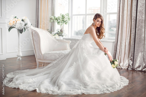 Fotografía  Bride in beautiful dress sitting resting on sofa indoors