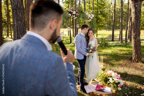 Fotografía  Leading or master of ceremonies, bride and groom at wedding ceremony with decora