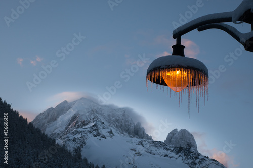 Snow and icicle covered amber lightpost against backdrop of wind Fototapeta