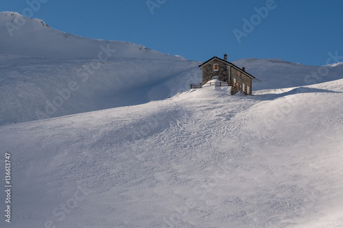 Fotografija  Alpine refuge below mountain ridge in winter on windswept snow u