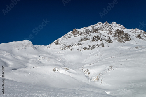 Foto op Plexiglas Alpinisme Fresh ski tracks leading down from alpine mountain ridge over gl