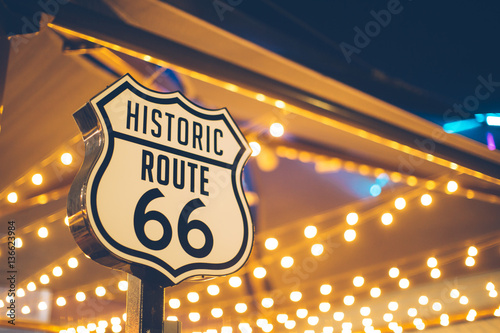 Photo Stands Route 66 Historic Route 66 sign in California with decoration lights on the background