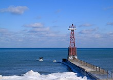 Lighthouse On A Pier Jutting Out Into An Icy Lake Michigan In Chicago During Winter.