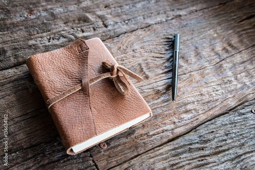 The leather book and pen on the wood table.