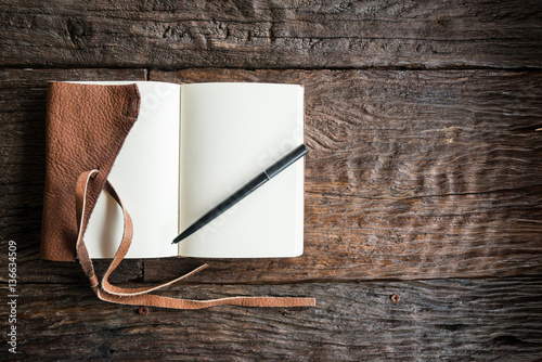 The leather book on the wood table.