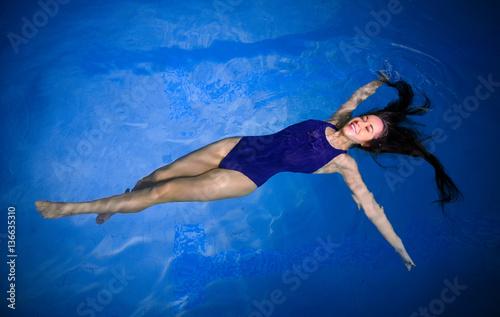 mloda-kobieta-w-niebieskim-stroju-unoszaca-sie-na-wodzie