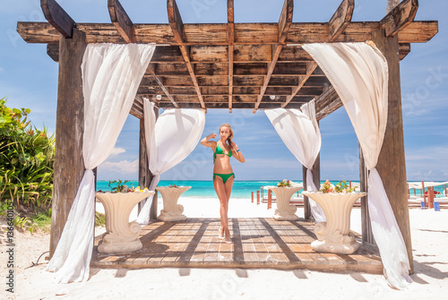 Fotografia  Woman at caribbean beach with pergola
