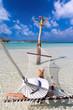 Frau mit weißem Hut relaxt auf einer Hängematte in tropischen Gewässern