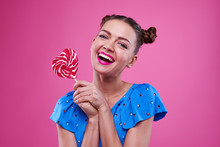 Smiley Girl Holding A Lollipop With Two Hands