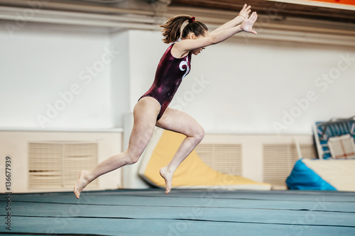 Photo Stands Gymnastics young girl athlete gymnast exercises floor competitions in gymnastics