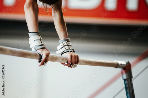 Tuinposter Gymnastiek hands young girl gymnast exercise on uneven bars