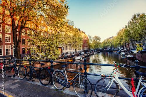 Fototapeta Bicycles Parked Along a Bridge Over the Canals of Amsterdam, Net obraz na płótnie