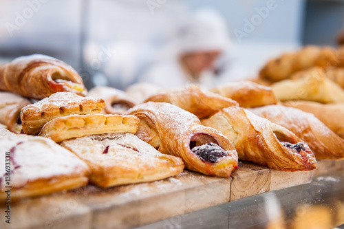 Close up freshly baked pastry goods on display in bakery shop. Selective focus