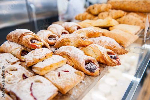 Foto op Canvas Brood Close up freshly baked pastry goods on display in bakery shop. Selective focus