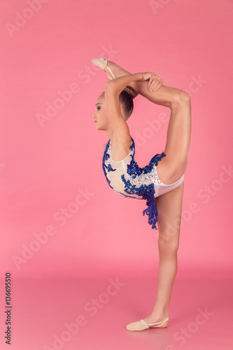 Foto op Aluminium Gymnastiek Teenage girl in blue dress doing gymnastic exercises on pink background.