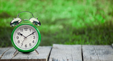 Green Clock On Old Wooden Table In The Summer Garden On A Sunny