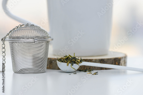 Fotografie, Obraz  Dry tea leaves in a teaspoon with Tea strainer and cup