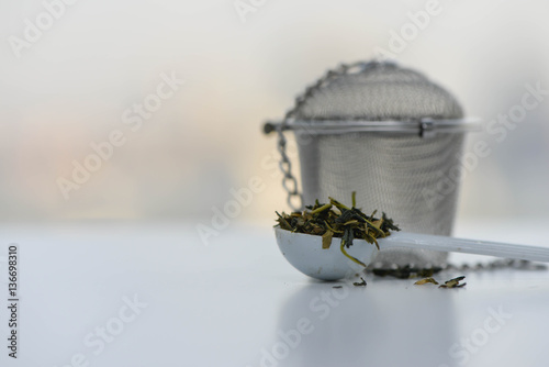 Fotografie, Obraz  Dry tea leaves in a teaspoon with Tea strainer