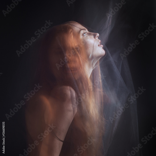 Canvas Print Beautiful model with red hair posing behind a black fabric and a veil in a studi