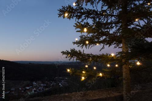 Fototapeta beleuchteter tannenbaum auf einem berg obraz na płótnie