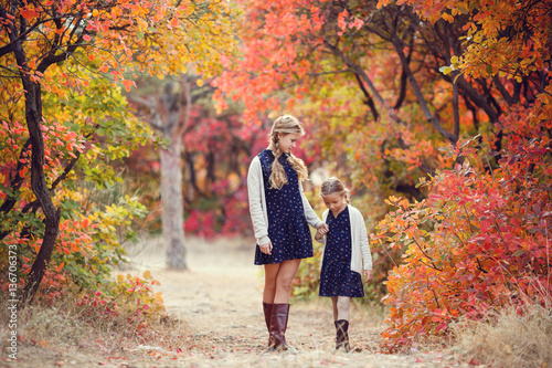 Fotografie, Tablou Two cheerful sisters playing in the park in warm autumn day