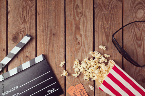 Movie clapper board, 3d glasses and popcorn on wooden background. Cinema concept.Top view from above