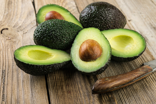 Fresh sliced avocado on wooden table. Vegetarian  food concept.