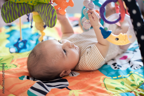 Fototapeta baby lying on Developing rug. obraz na płótnie