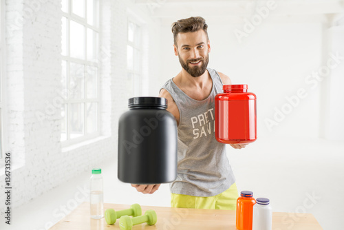 Fotografia  Athletic man holding bottles with sports nutriton in the white gym interior