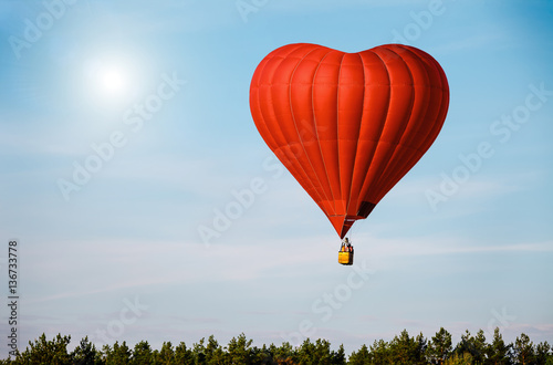 Poster Montgolfière / Dirigeable Beautiful red air balloon in the shape of heart against blue sky in a sunny bright day fly high above the trees. Romantic trip on Valentine's Day. Sports and recreation travel theme. Nature background